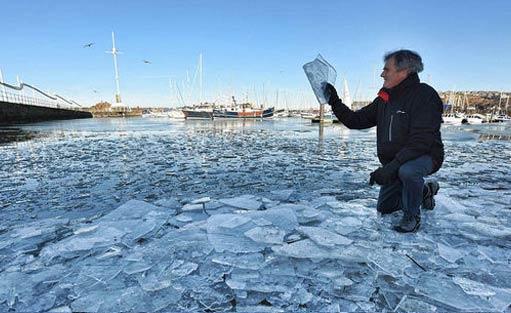 英国一海港因气温骤降海面结冰似玻璃碎片